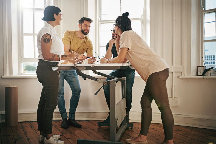 Shot of a team of designers brainstorming together around a drafting table